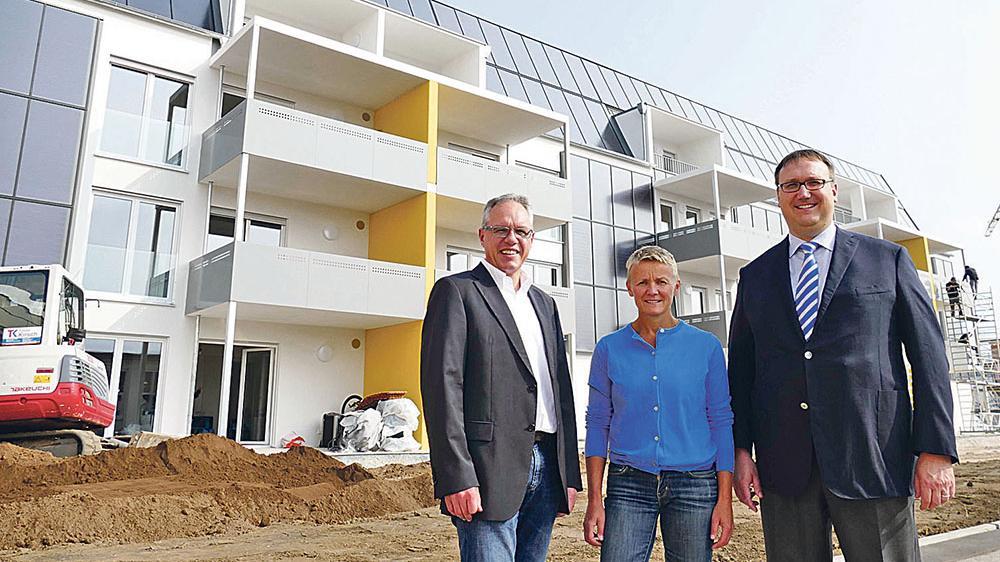 """Freuen sich, dass die insgesamt 19 Wohnungen der """"Sonnenhäuser"""" eineinhalb Jahre nach dem Spatenstich bereits bezogen werden: Architektin Michaela Bittner, Eigenheim-Vorstand Thomas Hanke (links) und Aufsichtsratsvorsitzender Bernd Körzendörfer (rechts). Das ökologische Vorzeigeprojekt ist bayernweit einmalig."""