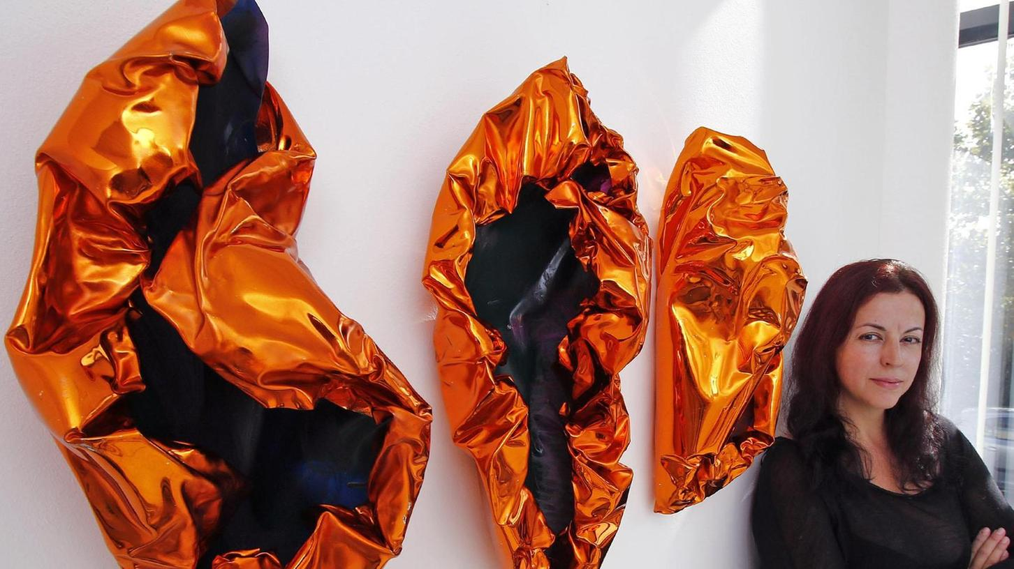 Die Künstlerin Elizabeth Thallauer vor einem Triptychon aus schillerndem Kunststoff. Damit regt sie zu einer spirituellen Auseinandersetzung an.