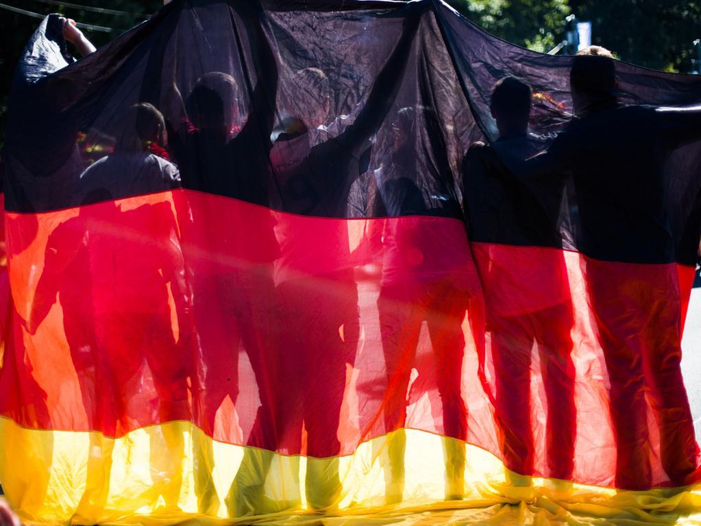 ARCHIV - Fans halten eine deutsche Fahne vor dem WM-Finale Deutschland-Argentinien am 13.07.2014 in Berlin. Spätestens seit dem WM-Sommermärchen vor zehn Jahren gibt es einen neuen Patriotismus in Deutschland. Foto: Maja Hitij/dpa (zu dpa Deutschsein ist gut, aber vielen eher unwichtig vom 16.09.2016) +++(c) dpa - Bildfunk+++