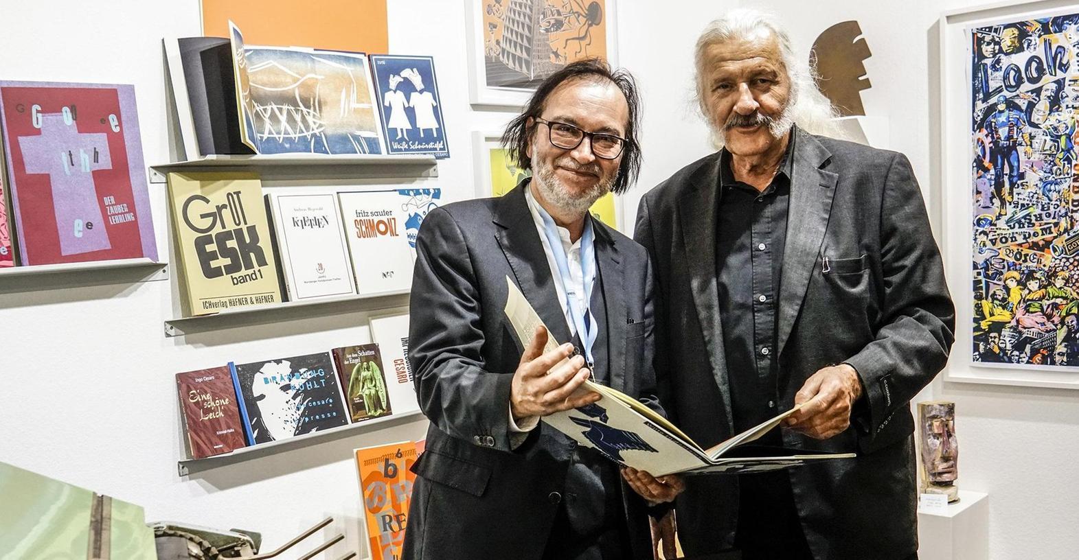 """Der Verleger Johannes Häfner (li.) und der Lyriker Ingo Cesaro präsentieren auf der Frankfurter Buchmesse das eigens für die Messe aufgelegte Kunstbuch """"Weiße Schnürstiefel"""". Im Vordergrund eine fast schon antike Handpresse."""