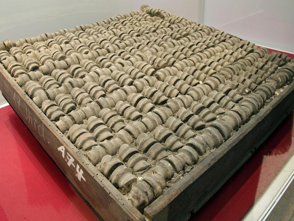 """Was sind wir bei der Hausarbeit heute verwöhnt mit pflegeleichten Fußböden! Einmal wischen und blitzblank ist der Belag aus Marmor, Holz, Beton oder Laminat. Man mag sich deshalb die Mühen gar nicht vorstellen, die jene Hausfrau im 16. oder 17. Jahrhundert beim Putztag aufbringen musste, in deren Haus diese große Bodenfliese lag. Denn das Bauteil besteht aus Knochen. Genauer gesagt aus Schafsknochen. Noch genauer gesagt aus Kniegelenken einer kleinen Herde. Die Nürnberger Fliese gehört zu den ältesten Beständen in der GNM-Sammlung. Schon 1868 beschrieb August Essenwein das ungewöhnliche Teil in einem Katalog. Als Herkunft nannte er ein """"Haus zu Mödling bei Wien"""". Datiert hatte der Architekt und Bauhistoriker die Knochenfliese auf das 17. Jahrhundert."""