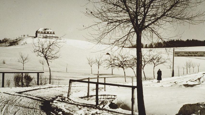 Der winterlich verschneite und noch fast völlig unbebaute Burgstall in Vorkriegszeiten. Oben auf dem Hügel befand sich einst eine Ausflugsgaststätte. Auf dem Banner am rechten Bildrand ist zu entziffern: