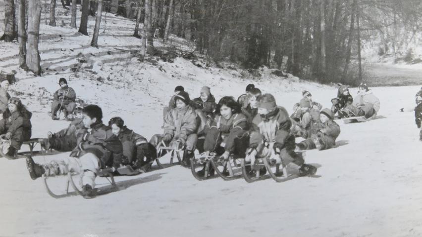 Rodelspaß, vermutlich im Heumöderntal. Der Kleidung und den Schlitten nach zu urteilen stammt das Foto dieser fröhlichen Kinderhorde in den 1970er oder 80er Jahren.