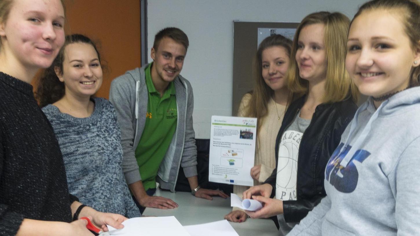 Praktisches Lernen: Maschinenbau-Student Philip Schreier (hinten) zeigt Schülerinnen, was mit Leichtbauweise möglich ist.