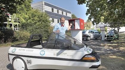 Der Hotelier des Hotels Luise mit seinem Elektromobil vor der Solartankstelle: An der Pforte des Hotels kann man den Schlüssel zu den Solarsteckdosen ausleihen.