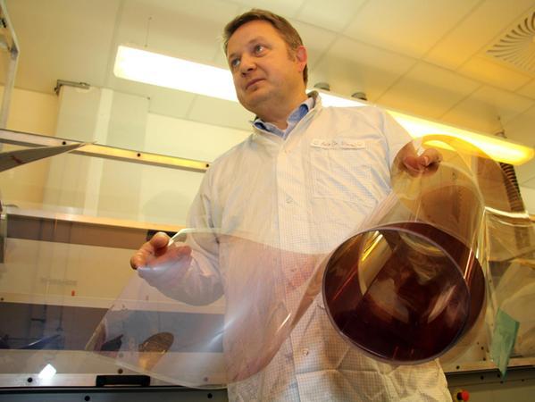 Die fertig beschichtete Solarfolie ist so dünn und biegsam, dass Jens Hauch sie aufrollen kann.
