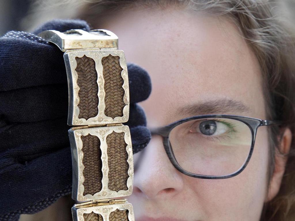 """Das ist ein wirklich spektakuläres Stück: Denn in seine zehn Glieder aus vergoldetem Silber sind geflochtene Haare eingelegt. Blonde, bräunliche, graue. """"Man begann im 17. Jahrhundert in England damit, Haare in Schmuckstücke einzuarbeiten"""", erklärt Anja Kregeloh aus der Textil- und Schmuck-Abteilung des Germanischen Nationalmuseums. """"Normalerweise wurde das Haar von nur einer Person eingearbeitet, erklärt die Expertin. Dass es bei dem Schmuckstück im Germanischen Strähnen von gleich zehn Menschen sind, hat einen guten Grund, wie Kregeloh recherchierte. Dabei halfen ihr die eingravierten Vornamen und Initialen auf der Rückseite der Metallglieder.  Das außergewöhnliche Armband war demnach das Geschenk eines Kaufmanns an seine Gattin, die damit die Haare ihrer zehn zum Zeitpunkt der Schmuckherstellung schon teilweise erwachsenen Kinder um den Arm tragen konnte."""