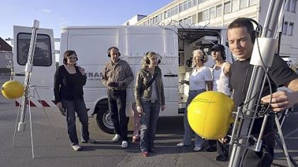 Florian Tuercke (rechts) mit seinen Instrumenten und den Zuhörern beim Auftakt zu seiner Deutschlandtour. Was aussieht wie ein Fernrohr mit Honigmelone, ist eine Art verkehrte E-Gitarre, die Schall aus der Umgebung sammelt.