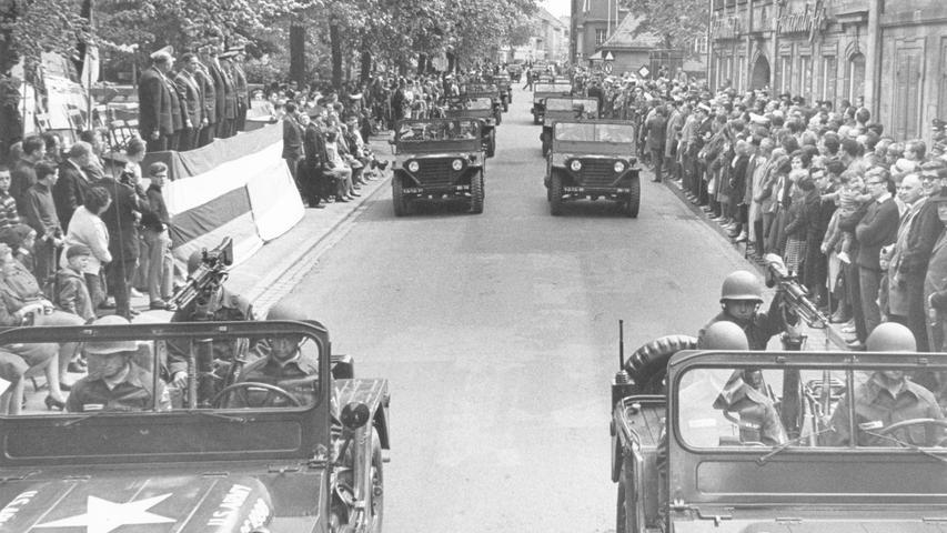 Was für ein Spektakel! Im Mai 1963 zeigt die US-Army bei einer Parade in der Deutsch-Amerikanischen Freundschaftswoche, was sie auf Lager hat. Der Zug fuhr durch die Straßen der Innenstadt, auf unserem Foto sieht man Hunderte Schaulustige am Bohlenplatz. Links im Bild die Armee-Oberen, die die Parade abnehmen.