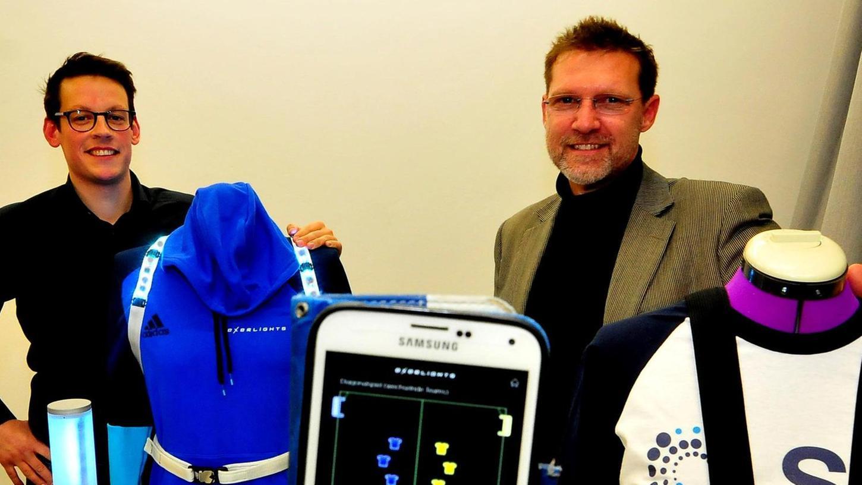 Julien Denis (li.) und Matthias Lochmann mit dem überarbeiteten leuchtenden Funktions-Modell und ihrem ersten Gurt-Prototypen (re.), die per Handy gesteuert werden.