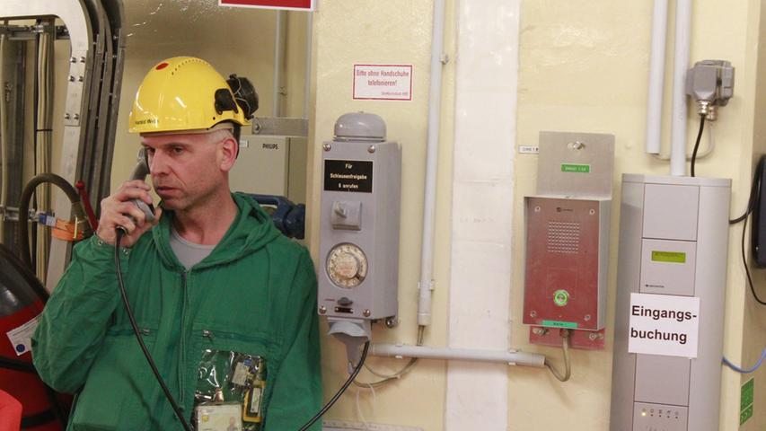 Wer grüne Arbeitskleidung im Atomkraftwerk trägt, ist für den Strahlenschutz zuständig. Der Mitarbeiter ruft durch, um Zutritt zur Schleuse zu erhalten.