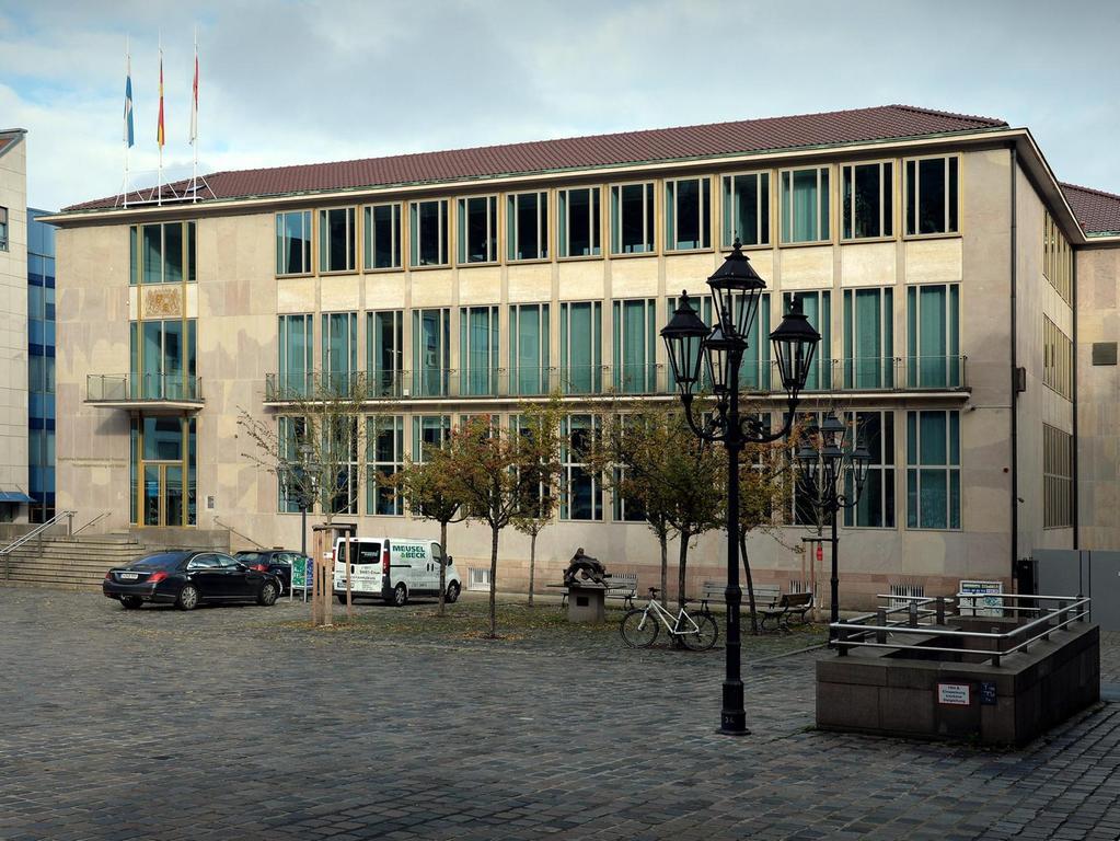 Die Staatsbank am Lorenzer Platz war eine beeindruckende Erscheinung. In dem Lindengarten davor verbrachten die Mitarbeiter oft ihre Pausen. Bei dem Bombenangriff im Januar 1945 wurde das Gebäude komplett zerstört. An seiner Stelle steht heute einer der qualitätsvollsten Bauten aus den fünfziger Jahren in Nürnberg. Derzeit ist dort das Heimatministerium untergebracht.