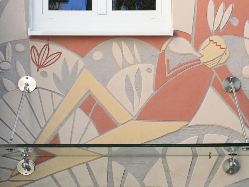 Dank Innendämmung konnten die alten Sgraffiti in der Hardstraße 48 und 50 gerettet werden. Über einem Hauseingang leert deshalb der fröhliche Zecher weiterhin ganz entspannt seinen Bocksbeutel Frankenwein.
