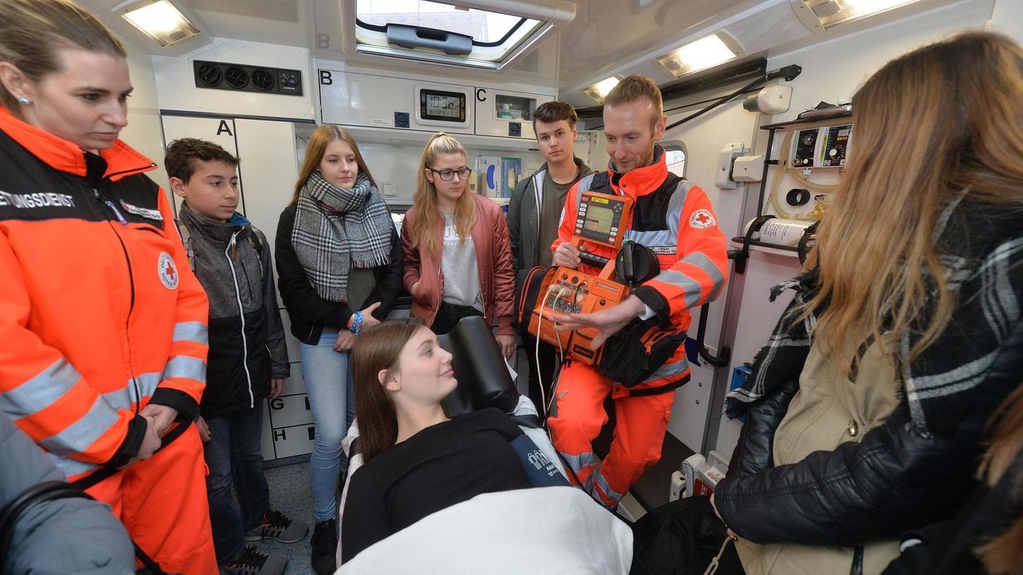 Wie arbeiten Rettungssanitäter? Tanja Regus (l.) und Max Jäger zeigen den Schülern, was im Rettungswagen zu tun ist. Eva Hußenether spielt die Kranke auf der Liege.