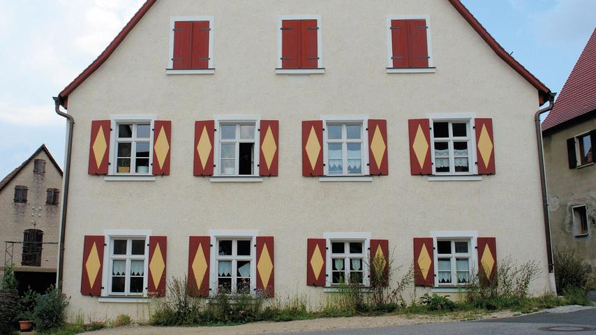 Vom Wohlstand, der im 19. Jahrhundert in Happurg aufgrund von Hopfenanbau und -handel herrschte, zeugt u. a. das stattliche Wohnstallhaus, das 1865 auf einem älteren Kern von 1766 errichtet worden ist. Es zählt zu den wenigen noch erhaltenen, ortstypischen Hopfenlagerhäusern mit mächtigen Dachspeichern. Die erbauungszeitliche Gebäudestruktur ist vollständig überliefert und von seiner originalen Ausstattung sind ebenfalls noch Teile vorhanden. Eine weitere Besonderheit, die in den letzten Jahren mehrfach im Nürnberger Land und in der Oberpfalz, vor allem bei repräsentativen Gebäuden, nachgewiesen werden konnte, stellt die auffällig gemusterte Fassade dar: rote und ockerfarbige Farbspritzer verteilen sich hier auf leicht getöntem Grund. 2012 hat ein Brand Dachstuhl und Dachgeschoss weitgehend zerstört. Bei der anschließenden Sanierung wurde unter anderem der Dachstuhl in seiner historisch überlieferten Konstruktionsweise komplett neu aufgerichtet. Die originalen Fachwerkwände haben der Eigentümer und sein Mieter aufwendig getrocknet, repariert und neu gefasst. Auch bei der Sanierung oder Erneuerung der restlichen Oberflächen – Böden, Türen, Decken – haben sich die beiden stark engagiert. Die sorgfältige und denkmalgerechte Instandsetzung der übriggebliebenen Bausubstanz ging weit über die notwendige Wiederherstellung von Wohnraum hinaus und hat den interessanten Bau wieder zu einem veritablen Hingucker gemacht.
