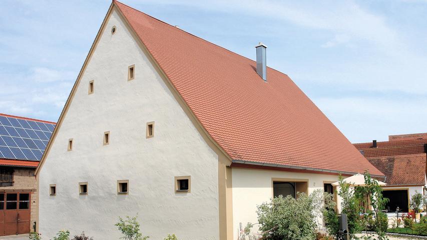 Wie enorm eine Fassadensanierung ein Gebäude aufwerten kann, zeigt sich deutlich am Anwesen Nr. 13 in Göppersdorf. Das historische Bauernhaus stammt aus dem 18. Jahrhundert. Es wurde als Wohnstallhaus über einem tonnengewölbten Keller aus Sandsteinquadern errichtet und bildet mit weiteren Wirtschaftsgebäuden einen Hofkomplex im Ortszentrum.  Der junge Eigentümer hat sich entschlossen, das Wohnstallhaus zu sanieren. Dabei lag ein Schwerpunkt auf der Aufarbeitung der Fassade. Aufgrund großer statischer Probleme im Dach musste die Renovierung hier beginnen. Im Anschluss legte der Eigentümer den ostseitigen Fachwerkgiebel frei. Der Eigentümer arbeitete die einzelnen Balken auf und verputzte die Gefache sowie das Erdgeschoss mit atmungsaktivem Kalkputz. Auch die drei übrigen Fassadenseiten erhielten einen neuen Putz. Bevor die Fassade abschließend neu getüncht wurde, setzte man denkmalgerechte Holzfenster in Dunkelbraun ein. Ihre Rahmungen sind gegenüber den helleren Fassadenflächen ockerfarben abgesetzt.
