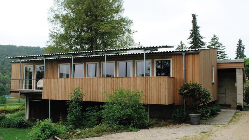 Das moderne Wohnhaus von 1958/61 war  für einen örtlichen Steinbruchbesitzer unter reichlichster Verwendung von regionalem Jurakalkstein errichtet worden. Der Entwurf der renommierten Stuttgarter Architekten Hans Kammerer und Walter Belz ist so individuell wie qualitätvoll.  Das denkmalgeschützte Gebäude besteht aus zwei Bauteilen mit flachen Pultdächern auf unterschiedlichen Ebenen. Der westliche Trakt mit Wohnzimmer und Küche ist aus Kalkstein aufgemauert, der östliche birgt Schlafzimmer und Bäder und ist als Holzständerbau errichtet.  Die hochwertige Ausstattung war nahezu ungeschmälert erhalten. Nur: Das Haus galt als nicht mehr bewohnbar, weil man es kaum heizen konnte. Die Gebäudedämmung aus den 1960er Jahren war mehr als dürftig – selbst durch Wände und Decken zog der Wind. Nach langer Tüftelei hatte der fachkundige Eigentümer eine durchdachte Lösung erarbeitet: Um die repräsentative Holzdecke im Wohntrakt zu schonen, wurde die Dämmschicht zwischen Wellblechdach und Holzdecke verlegt. Im hölzernen Bauteil wurde die Dämmung in den Hohlraum zwischen Innen- und Außenwand gefügt. Hier sorgen neue, perfekt eingepasste Holzfenster für zusätzliche Abdichtung. Die wenigen Zugeständnisse an zeitgemäßes Wohnen betrafen geringfügige Modernisierungen in den Badezimmern und die Ostseite des Holzständerbaus, wo ein schmaler Balkon angefügt worden ist.
