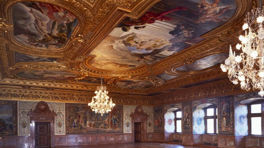 """Von 1535 bis 1537 hat sich Markgraf Georg der Fromme Schloss Ratibor in Roth errichten lassen. Immer wieder wurde das Schloss verändert, bis es 1791 in die Hände des vermögenden Industriellen Johann Philipp Stieber gelangte. Dieser hat hier sowohl Wohnräume als auch seine Tressenmanufaktur untergebracht. Gegen Ende des 19. Jahrhunderts hat seine Familie den Bau tiefgreifend verändern lassen. Prachtvollster Raum ist der riesige """"Prunksaal"""" im ersten Stock, geschaffen nach venezianischem Vorbild, ausgestattet mit reichstem Deckenstuck, Deckengemälden, Wandmalereien und einem wertvollen Intarsienboden. Weil sich dieser Boden merklich gesenkt hatte, hat die Stadt Roth als Eigentümerin des Schlosses erste Untersuchungen beauftragt. Eine  Radaruntersuchung offenbarte starke statische Schäden, die daher rührten, dass die darunterliegende Deckenkonstruktion der ursprünglich im Erdgeschoss vorhandenen Halle von Anfang an zu schwach ausgelegt war. Balken waren gebrochen und auch der Holzwurm hatte gefressen.   Um den Intarsienboden zu schonen, entschied man sich zu einer Sanierung von unten. Nach Abnahme der Deckenverkleidung kam hier außerdem die bauzeitliche Bohlenbalkendecke zum Vorschein – eine Sensation! Im südwestlichen Teil des Erdgeschosses ist die Holzdecke sichtbar geblieben und wurde sorgfältig aufgearbeitet. Sämtliche Räume im Erdgeschoss erhielten einen passenden Ziegelboden und ihre Wände wurden überschlämmt. Jetzt werden die Räumlichkeiten im Erdgeschoss als Bürgerbegegnungszentrum für Feierlichkeiten aller Art genutzt."""