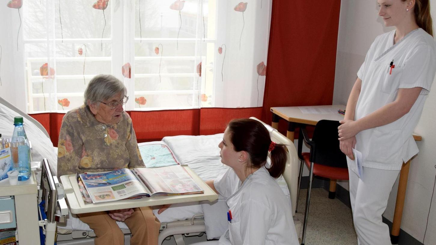 Schichtwechsel am Bett: Auszubildende Eva Pongratz (Mitte) informiert eine Patientin über ihre Ablösung durch Julia Nitsche (rechts).