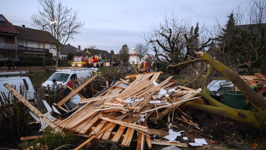 Feuerwehrleute und Anwohner räumen am 09.03.17 in Kürnach (Bayern) einem Wohngebiet die Schäden auf, die am späten Nachmittag eine Windhose angerichtet hatte. Um die 20 Häuser und Lauben waren durch den Sturm zu Schaden gekommen. Verletzt wurde niemand. Der Tornado hatte sich am späten Nachmittag zeitlich und räumlich eng begrenzt innerhalb einer Gewitterzelle entwickelt. Die Schadenshöhe war zunächst nicht zu beziffern.(zu dpa «Tornado über Unterfranken - Unwetterwarnung für mehrere Landkreise» vom 09.03.2017) Foto: Daniel Peter/www.danielpeter.net/dpa +++(c) dpa - Bildfunk+++