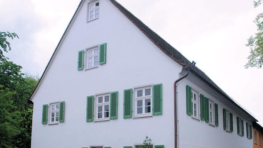 Die ehemalige Kaserne gehört ebenfalls zum Gelände des einstmaligen Dominikanerinnenklosters, das die wechselvolle Geschichte Frauenaurachs komprimiert widerspiegelt. Das hier ab 1616 gebaute Schloss diente unter anderem als provisorische Unterbringung für hugenottische Glaubensflüchtlinge. Mit dem Ausbau des nahen Erlangens zur markgräflichen Residenz verlor das Frauenauracher Schloss an Bedeutung und wurde 1710 bis 1780 als Kaserne genutzt, später als Getreidemagazin. Durch den 1862 schließlich durchgeführten Abriss ging allerdings nicht der gesamte, ursprünglich zur Gesamtanlage gehörende Bestand verloren. Bei dem heute zu Wohnzwecken genutzten Gebäude Brauhofgasse Nr. 8, ein zweigeschossiger Satteldachbau mit Fachwerkobergeschoss, handelt es sich um einen Teil der ehemaligen Kaserne. Das, was an historischer Bausubstanz überliefert war, wurde mit äußerster Sorgfalt überarbeitet. Schäden am Dach und insbesondere an den Treppen wurden fachgerecht behoben. Der behutsame Umgang mit dem noch erhaltenen Bestand zeichnet insgesamt auch diese vorbildliche Gesamtsanierung aus.