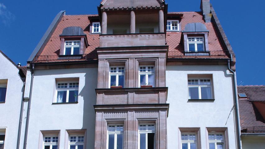 """Innerhalb der Nürnberger Stadtmauer wurde 1909/10 in der Engelhardsgasse 27 ein viergeschossiges Mietshaus nach Plänen des Architekten Hans Müller (1864–1951) errichtet. Die symmetrisch gegliederte Straßenfassade mit geschossübergreifendem Erkeranbau ruht im Erdgeschoss auf einem mächtigen Sandsteinsockel mit zwei dominierenden Korbbogenfenstern. Eklektizistische Details wie etwa die beiden Bildnismedaillons am Erker und weitere Bauornamentik reflektieren noch den sog. """"Nürnberger Stil"""", eine lokalspezifische Sonderform des Historismus, der auf die Erhaltung des spezifischen Charakters der Altstadt zielte. Auch der über die Stadtmauer hinweg sichtbare, durch gotisierende Ziegelmauerwerksbögen gegliederte südliche Hausgiebel stützt diese Intention. Unter der heute vollflächig überputzten Rückfassade verbirgt sich jedoch eine damals neuartige Konstruktion eines Eisenfachwerks aus industriell vorgefertigten Eisenträgern mit Backsteingefachen. Bei der vollständigen Überarbeitung 2014/15 wurde auch das Rückgebäude einbezogen. Bei den Maßnahmen wurden unter anderem das Dachtragwerk und die Fassaden saniert. Die bauzeitliche Grundrissstruktur sowie alle im Inneren noch vorhandenen historischen Bauteile hat man erhalten und aufwändig restauriert. In die ehemaligen Toilettenräume, die wie in Mietshäusern der Zeit allgemein üblich, als Außenklosetts im Hausflur angelegt waren, wurde ein Aufzug eingebaut. Brandspuren im Holzboden des Treppenhauses verweisen heute noch auf den Zweiten Weltkrieg, bei dem das Gebäude schwer beschädigt wurde. Diesen bewussten Umgang des Eigentümers mit der Vergangenheit lobt der Bezirk Mittelfranken besonders."""