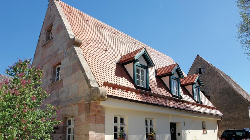 Das ehemalige Wohnstallhaus aus der Mitte des 18. Jahrhunderts (1745/46) im heute zu Nürnberg gehörenden Dorf Neunhof bei Kraftshof wurde nach jahrelangem Leerstand umfangreich saniert. Der teilverputzte, eingeschossige Sandsteinquaderbau mit Satteldach und auskragender Traufe zeichnet sich vor allem durch seinen Voluten-Ziergiebel an der Westfassade aus, eine charakteristische Besonderheit, die in dieser Form nur im Umland von Nürnberg zu finden ist. Die zur ebenfalls denkmalgeschützten Scheune (bez. 1725) gerichtete Ostfassade wurde in Fachwerk errichtet. Auf Grundlage der umfangreich überlieferten Bausubstanz und ausführlicher Befunde wurde das Bauernhaus zu einem Wohnhaus umgebaut. Der in ursprünglicher Konstruktion erhaltene Dachstuhl wurde fachgerecht instand gesetzt, die bauzeitlichen Grundrissstrukturen wurden beibehalten. Zur Nutzung und Belichtung des ehemaligen Stallbereichs, dem zukünftigen Wohnzimmer, hat man bewusst ein modernes Bindeglied mit dunkel beschichteten Metallfenstern implementiert. Als anschaulicher Verweis auf die Vergangenheit dienen die aufgearbeitete Bohlenbalkendecke und die sichtbar gebliebenen, zahlreichen geritzten und verzierten Strohlehmgefache der Fachwerkwände. Der Bezirk Mittelfranken würdigt die Sanierung als