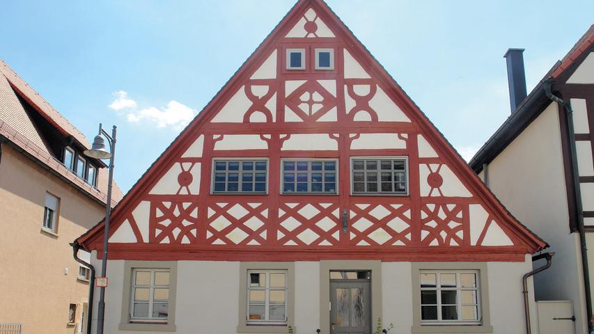 Im Ortskern von Markt Bibart ist das Straßenbild entlang der Nürnberger Straße geprägt von einem Ensemble aus ein bis zweigeschossigen Fachwerkbauten, teilweise aus dem 17. Jahrhundert, sowie einigen Walm- und Mansarddachhäusern aus dem 18. Jahrhundert. Zu dieser Reihe von Häusern, die größtenteils mit dem Giebel zur breiten Hauptdurchgangsstraße gerichtet sind, zählt auch das kleine Wohnhaus Nr. 4 mit seinem auffälligen Schmuckfachwerk.   Vor seiner Sanierung war das im Kern aus dem 17. Jahrhundert stammende Gebäude sehr heruntergekommen. 1940 hatte ein Umbau, bei dem auch das Fachwerk im Erdgeschoss entfernt wurde, das Erscheinungsbild verändert und das Haus in zwei unabhängige Wohneinheiten aufgeteilt. Bei diesem unsensiblen Eingriff blieb der mit Gestaltungselementen wie Rosetten, durchkreuzten Rauten, Feuerböcken und geschweiften Kopfbändern reichverzierte Giebel glücklicherweise unbeeinträchtigt.   Zu Beginn der Maßnahme wurden alle Schäden dokumentiert. Das Dach hat man nach Reparatur und maßvoller Dämmung neu gedeckt. Das Giebelfachwerk war teils durchfeuchtet, verfault und stellenweise nicht mehr tragfähig. Der frühere Einsatz von ungeeigneten Materialien wie PU-Schaum und Silikon hatte die Situation verschlechtert. Alle Holzteile und die Putzgefache konnten fachmännisch repariert oder erneuert werden. Querrechteckige, in das Fachwerk eingepasste Fenster stellen die einstige Fassadenwirkung wieder her.   Im Inneren des Wohnhauses hat man alle beschädigten Oberflächen saniert. Auch die überlieferte Bohlenbalkendecke im Erdgeschoss wurde aufgearbeitet. Bausünden aus früheren Jahren wie Verkleidungen, abgehängte Decken, Zwischenwände u. ä. wurden rückgebaut. Bei allen Arbeiten wurde lobenswerterweise möglichst viel an überliefertem Bestand erhalten.  Das denkmalpflegerische Einfühlungsvermögen zeigt sich auch bei der Materialauswahl und an Details wie handgeschmiedeten Handläufen oder historischen Türbeschlägen. Mit der Sanierung dieses kleinen Schmuckstückes 