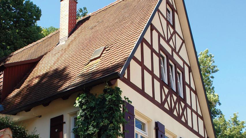 Dinkelsbühl war einst vollständig von einer Stadtmauer umgeben. Sie zählt deutschlandweit zu den am besten erhaltenen spätmittelalterlichen Befestigungen. Anbauten an diesen Mauergürtel waren strikt verboten. Das Anwesen Kapuzinergasse 9 bildet aber eine Ausnahme, denn immerhin errichtete es der damalige Stadtbaumeister für sich und seine Familie. Während das Wohnhaus erst 1900 entstand, stammt das Gartenhäuschen noch aus dem 18. Jahrhundert. Von Westen begrenzt die Stadtmauer beide Bauten und das Gartengrundstück.  Vor allem das Gartenhaus – ein kleiner, zweigeschossiger Putzbau auf drei mal drei Metern Grundfläche mit Walmdach – war wegen eindringender Feuchtigkeit in keinem guten Zustand und wurde von den Eigentümern zuletzt nur noch als Abstellraum genutzt. 2012 bis 2014 unterzogen sie das gesamte Anwesen einer Sanierung, in deren Zuge das Gartenhäuschen eine Umnutzung zum Gästehaus erfuhr. Nachdem ihm ein stabiler Dachstuhl aufgesetzt worden war, wurde sein Dach unter Verwendung der alten Biberschwanzziegel neu gedeckt. An seine Ostseite wurde ein neuer Anbau mit Glasfronten und Schwebetüren gefügt. Da an gleicher Stelle vorher ein Holzschuppen stand und man diesen Charakter beibehalten wollte, wurde der Anbau mit Holzlatten verkleidet.  Bis zuletzt konnte man das Obergeschoss des Gartenhäuschens nur über eine Außentreppe erreichen. Diese wurde entfernt und durch eine Verbindungstreppe im Inneren ersetzt. Anstelle der ehemaligen Zugangstür zieren nun zwei neue Holzfenster die Fassade.  Sowohl im Gartenhaus als auch im Wohnhaus wurde die angrenzende, ehemals verputzte Stadtmauer freigelegt. Sie wirkt in Verbindung mit den Solnhofener Fußbodenplatten stimmig und passt hervorragend zu den fachgerecht aufgearbeiteten Böden, Türen und der Treppe des Wohnhauses. Letzterem verleihen neue Holzfenster im Dinkelsbühler Stil ein optisch vorbildliches Gewand, wobei weder das Wohnhaus noch das Gartenhaus durch die Eingriffe an Außenwirkung einbüßten. Die denkmalgerechte Maß