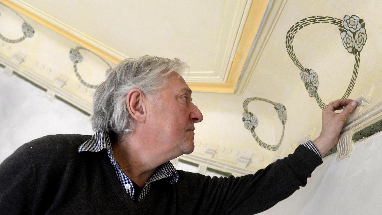 Der Nürnberger Kunstmaler Béla Faragó arbeitet mit dem Skalpell an einem historischen Deckenfries im ehemaligen Humbser-Verwaltungsgebäude. Mit Silber-Schlagmetall hat er das Blumendekor restauriert.