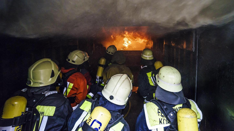 Der Container ist innen schon schwarz und strahlt enorme Hitze ab — Teilnehmer der Übung sitzen mit dem Ausbildungsleiter im Rauch und lernen, das Feuer zu bändigen ohne selbst in Gefahr zu geraten.