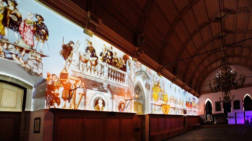 Quer durch die Kunstgattungen war Dürer tätig: Er malte und zeichnete nicht nur, sondern lieferte auch Entwürfe, die anschließend von spezialisierten Künstlern wie Wand- oder Glasmalern oder Bildhauern ausgeführt wurden. Der prestigeträchtigste Auftrag, den die Stadt Nürnberg zu Beginn der 1520er Jahre vergeben konnte, war die Leitung der künstlerischen Neuausstattung des Rathauses.  Die Mammutaufgabe ging an Dürer. Das Foto zeigt die städtische Aktion, bei der die Malereien vor einigen Jahren auf die Rathauswand projiziert wurden.