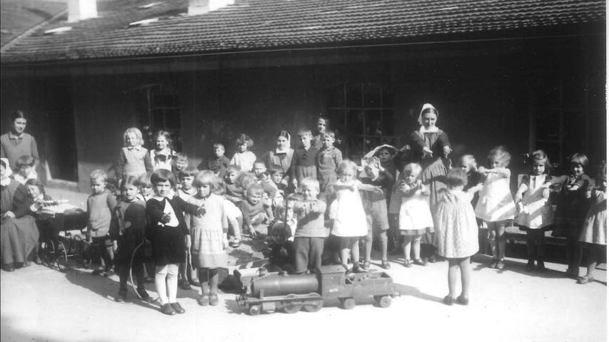 Bewegung an der frischen Luft tut gut, das wussten die Kindergärtnerinnen auch schon Anfang der 1930er Jahre. Die Kinder hätten wahrscheinlich lieber mit der tollen Lokomotive gespielt oder im Sandkasten gebuddelt, anstatt Kniebeugen zu machen.