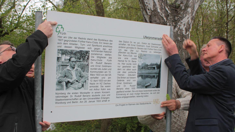 Oberbürgermeister Thomas Jung (rechts) half beim Anbringen der erneuerten Erinnerungstafel an der Uferpromenade.