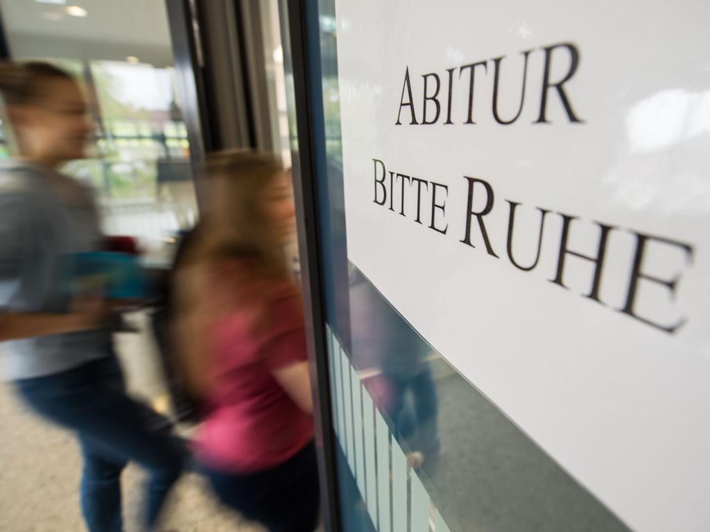 Zwei Schülerinnen gehen am 25.04.2017 im Solitude-Gymnasium in Stuttgart (Baden-Württemberg) auf dem Weg zum Prüfungsraum an einem Schild mit der Aufschrift