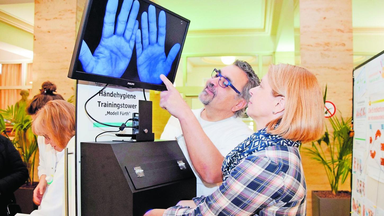 Im Rahmen einer Aktion anlässlich des internationalen Tags der Händehygiene zeigt Fachkraft Klaus Schmidt-Drempetic einer Besucherin, wie man per UV-Schwarzlicht das Ergebnis der Desinfektion überprüfen kann.