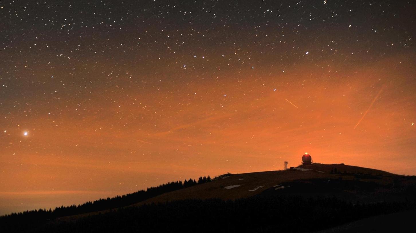 Die Nachtaufnahme zeigt die Radarstation auf der Wasserkuppe unter einem klaren Sternenhimmel. Außer an entlegenen Orten überstrahlen vielerorts meist Lichter die natürliche Dunkelheit. Das schadet nachtaktiven Tieren.