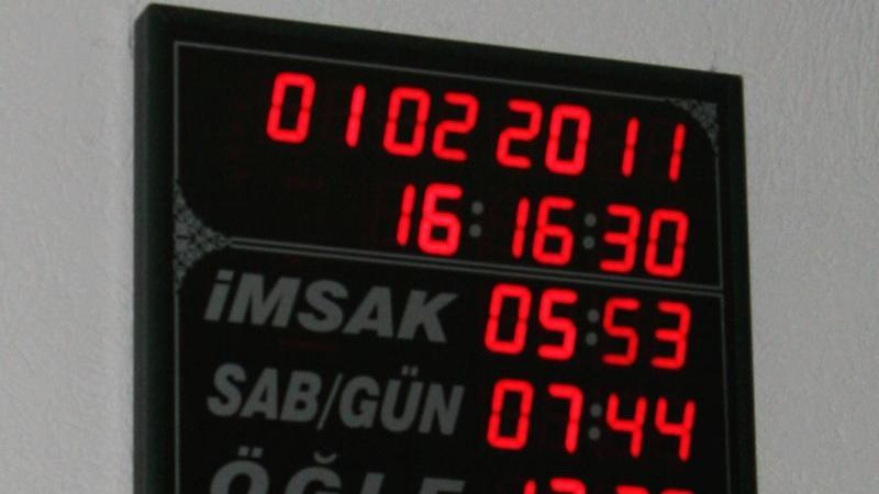 Die Zeit stets im Blick: Eine digitale Uhrentafel im Foyer zeigt den Besuchern die Zeitabschnitte, in denen das Gebet abgehalten wird. Neben Datum und Uhrzeit sehen die Moscheebesucher den Zeitpunkt der Morgendämmerung, sowie Sonnenaufgang und die Zeiten für Mittags-, Nachmittags-, Abend- und Nachtgebet. Die letzte Zeile deutet die momentane Außentemperatur.