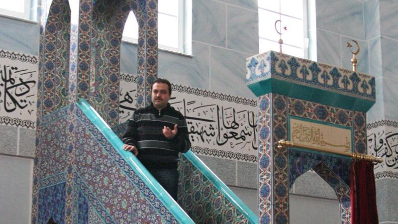Ümit Canlı, Bildungsleiter und Dialogbeauftragter der Eyüp-Sultan-Moschee in Nürnberg, führt den Besuchern die Predigtkanzel vor, die sogenannte