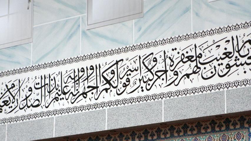 Arabische Schriftzeichen: Zahlreiche Suren (Verse) aus dem heiligen Buch der Muslime, dem Koran, zieren die Wände des islamischen Gotteshauses. Jede Moschee sieht anders aus. Ihr Erscheinungsbild richtet sich nach der jeweiligen kulturellen Prägung der Gemeinde. Die Eyüp-Sultan-Moschee ist türkisch geprägt und existiert seit 1991. Zum Freitagsgebet finden sich bis zu 2000 Gläubige in der Gemeinde ein. Zum Feiertagsgebet nach dem Fastenmonat Ramadan kommen sogar bis zu 6000 Gläubige und füllen die Moschee samt allen Nebenräumen, Korridoren und dem Innenhof im Freien.