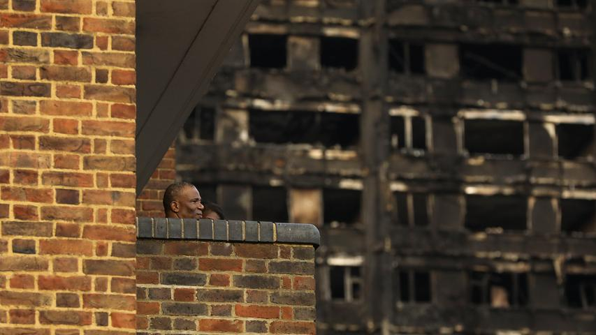A man stands on his balcony in front of the burnt out shell of the Grenfell apartment tower block in North Kensington, London, Britain, June 18, 2017. REUTERS/Marko Djurica