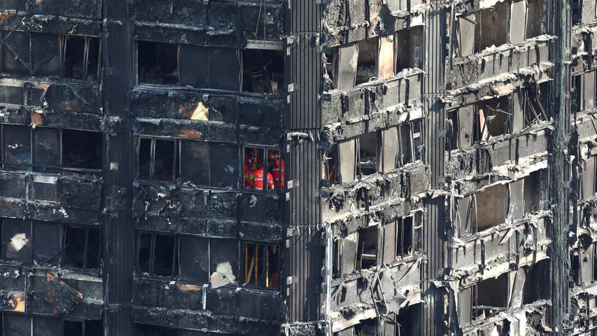 Members of the emergency services work inside burnt out remains of the Grenfell apartment tower in North Kensington, London, Britain, June 18, 2017. REUTERS/Neil Hall TPX IMAGES OF THE DAY