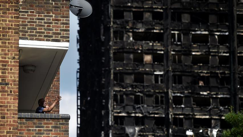 A man stands on his balcony in front of the burnt out shell of the Grenfell apartment tower block in North Kensington, London, Britain, June 17, 2017. REUTERS/Hannah McKay