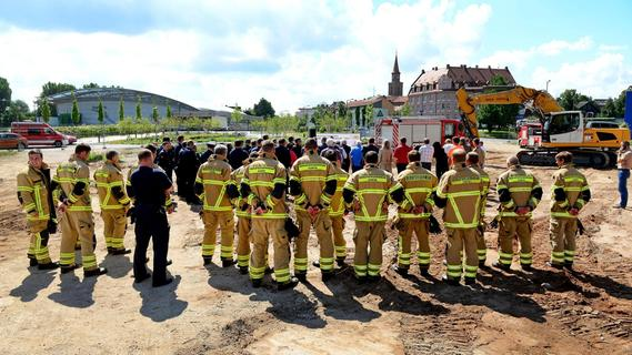 Feuerwehrleute und Vertreter der Stadtspitze versammelten sich auf dem Brachgelände am Schießanger, um dem Spatenstich für die neue Feuerwache beizuwohnen.