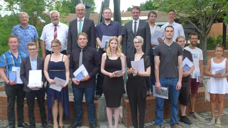 Das Foto zeigt die 13 Staatspreisträger und die beiden Klassenbesten der Abschlussklassen zusammen mit Schulleiter Michael Greiner, den stellvertretenden Landrat Walter Schnell, Kreishandwerksmeister Hanno Dietrich und Martin Eckmann von der IHK Nürnberg.