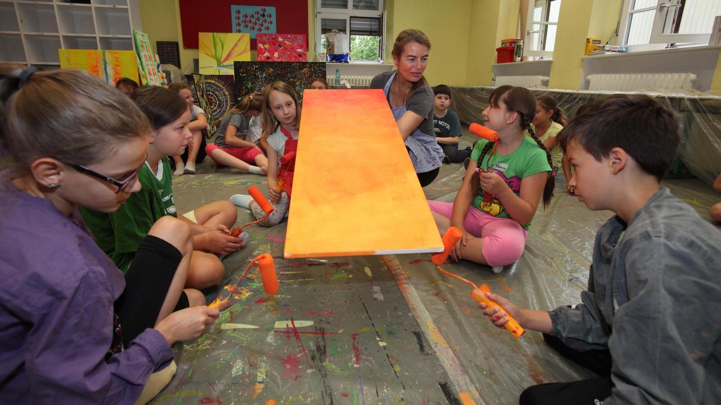 Volle Konzentration: Mit Interesse lernen die Schülerinnen und Schüler in ihrem Atelier-Klassezimmer von der Künstlerin Sabine Schwarz und üben sich im Malen. Im Hintergrund sind die bereits fertigen Werke zu sehen.