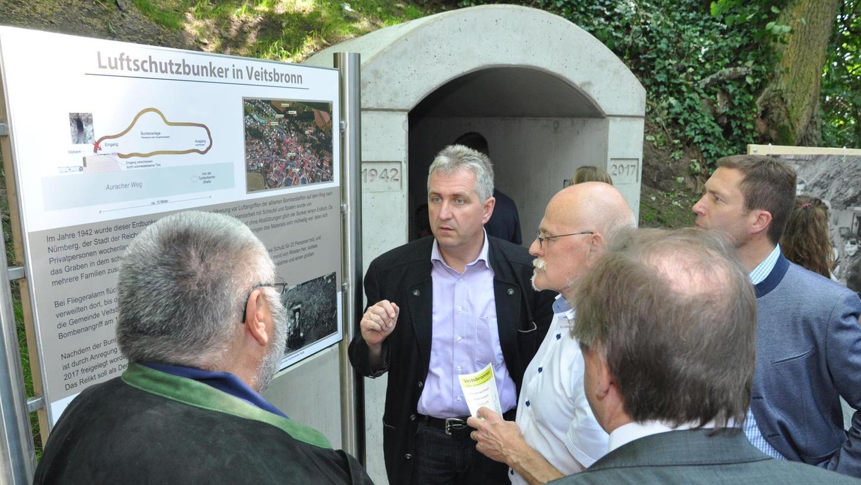 Gemeindeheimatpfleger Alfred Strunz (links) erläutert den Eröffnungsgästen — unter ihnen etliche Politiker — Einzelheiten zum Luftschutzbunker am Auracher Weg in Veitsbronn.