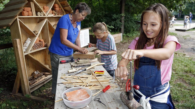 Wir bauen ein Insektenhotel: Die neunjährige Adana (vorne) bohrt Löcher in ein Holzstück, auch die siebenjährige Jamila hilft eifrig mit. Kursleiterin Annett Langer (links) informiert die jungen Besucher, was man beim Bau eines Insektenhotels alles beachten muss.