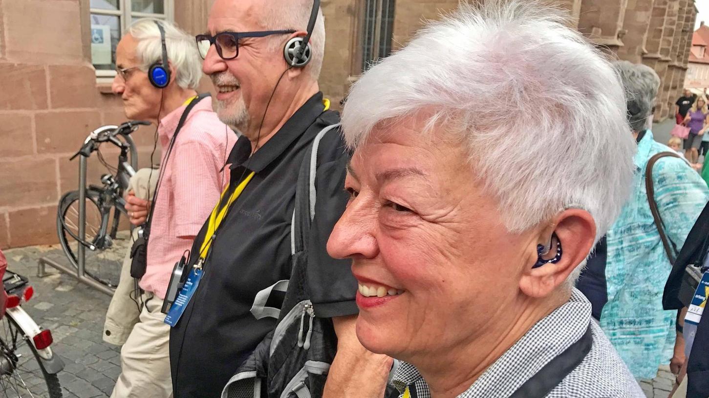 Auf dem Bild ist vorne Mechthild Haferung mit Hörgerät zu sehen. Daneben zwei hörende Männer jeweils mit Kopfhörer.