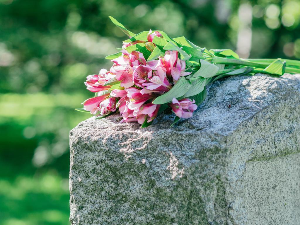 Motiv: Blumenstrauß liegt auf Grabstein - Friedhof - Symbolbild Tod- Sterben ..Headstone in cemetery with flowers for concept of death and loss..Foto: jrwasserman - Fotolia (komplett nennen!); - 2015 gesp. ..10 credits für Kollektiv - KST 4110